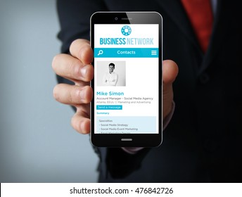 Business concept: businessman hand holding a touch phone with Business network web on the screen