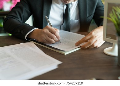 Business concept: Businessman sitting at coffee shop. is writing signs a contract. Holding pen in hand