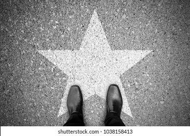 Business concept. Businessman standing on the street and star sign on the floor.