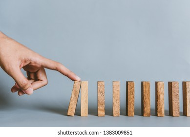Business concept. The businessman's fingers are starting domino effect