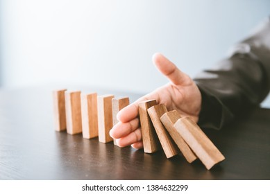 Business concept. The businessman's fingers are Stopping domino effect.