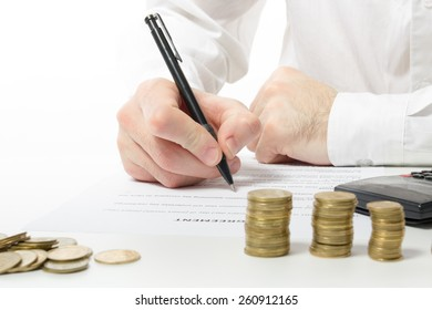 Business concept. Businessman's hand counting money on calculator and signing documents at office workplace, office work. Stack of coins. Financial Accounting - money and calculator.