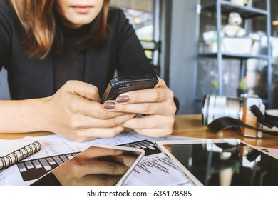 business concept. businesswomen sitting at table in coffe shop, using smartphones and discuss business strategy with soft-focus in the background. over light