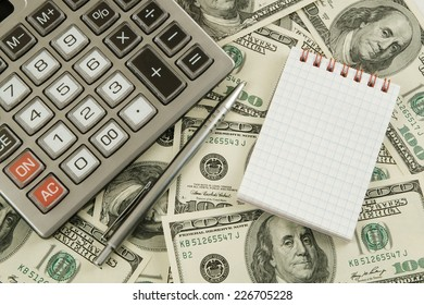 Business concept, calculator and notebook on money background