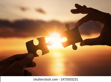 Business concept. Close up of hands connecting two pieces of jigsaw puzzle over the beautiful sunset