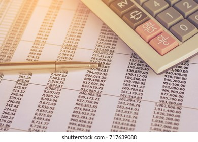 Business concept : close up pen on finance report and calculator on table office.