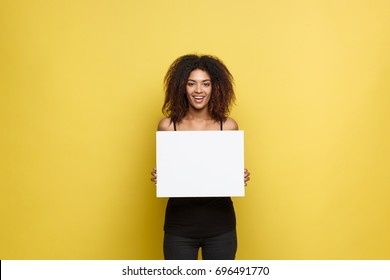 Business Concept - Close up Portrait young beautiful attractive African American smiling showing plain white blank sign. Yellow Pastel studio Background. Copy space.
