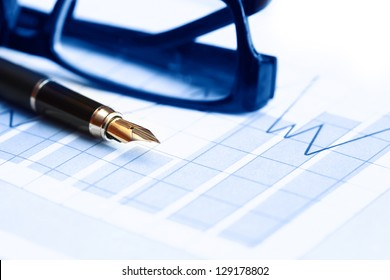Business concept. Closeup of fountain pen near spectacles on paper background with business chart