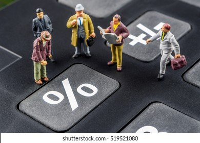 business concept, closeup of miniature figurine of businessmen discussing on big black calculator about interest rates / percentage changes