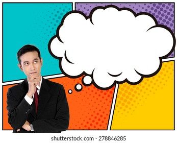 Business concept in comic style. Young Asian businessman looking up to empty thinking bubble above him, on colorful comic panels background