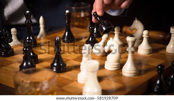 Business concept. Competition between companies, enterprises, firms. Closeup of chess pieces on chessboard. Men playing chess in restaurant.