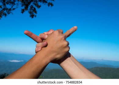 Business concept conflict, unlike, not agree helping together, hand holding with blue sky and mountain background