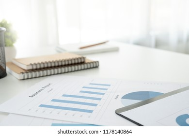 Business concept with copy space. Office desk table with pen focus and analysis chart, cup of coffee on desk.Selective focus.