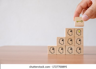 Business concept of creative idea and innovation. Hand picked wooden cube with key icon over wood block with lamp icon (new idea)  and head human symbol have no idea