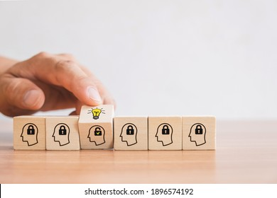 Business concept of creative idea and innovation. Hand picked wooden cube block with unlock icon (new idea) and head human symbol have lock idea.