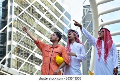 Business concept : The engineer standing together with Arab investor with modern city background