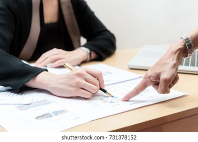 Business concept, Finger of hand and pen  point at graph in paper  among document laptop for order in office.