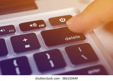 Business concept  finger pressing delete key on  keyboard.