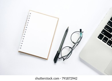 Business concept -  Flat lay top view of laptop, glasses, notepad & pen with copy space on white desk table.