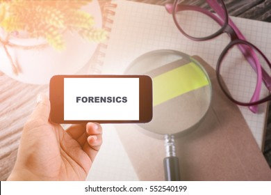 Business Concept : FORENSICS word on smartphone with office table background