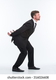 Business concept. Full length studio shot of a well dressed businessman pretending to carry a heavy invisible load on his back.