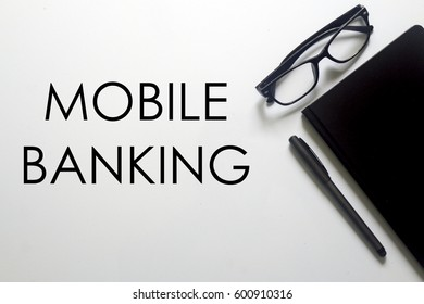 A business concept. A glasses, pen and notebook with MOBILE BANKING written on white background.