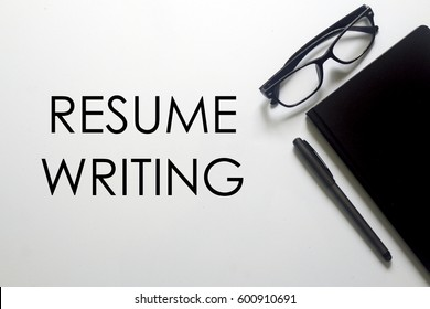 A business concept. A glasses, pen and notebook with RESUME WRITING written on white background.