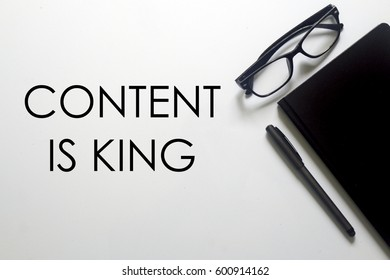 A business concept. A glasses, pen and notebook with CONTENT IS KING written on white background.