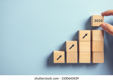 Business concept growth 2020 success process, Close up Woman hand arranging wood block stacking as step stair on paper blue background, copy space.