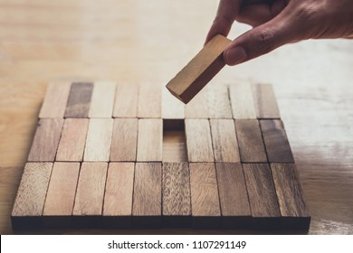 Business concept for growth success process, Images of hand of businesspeople placing and pulling wood block to complete in game and success in strategy.