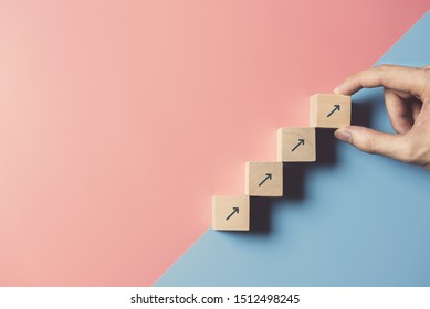 Business concept growth success process, Close up man hand arranging wood block stacking as step stair on paper blue and pink background, copy space. - Shutterstock ID 1512498245