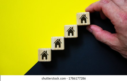 Business concept growth success process. Wood block stacking as step stair on paper yellow and black background, copy space.  House icon. Male hand.