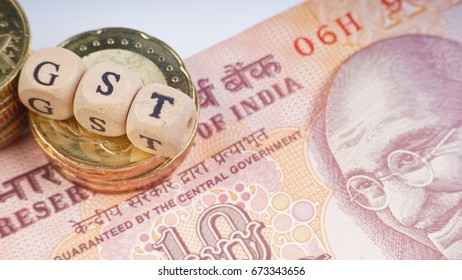 Business Concept with a GST word on stacked coins and rupee.Closeup crop segment and selective focus.