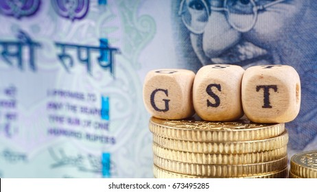 Business Concept with a GST word on a wooden cube,coins and rupee notes.Closeup crop segment and selective focus.