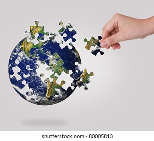 Business concept with a hand building puzzle globe