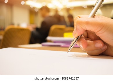 Business Concept : Hand Businessman holding silver pen to taking notes on white paperwork or Document at conference meeting room in seminar on indoors blur people background
