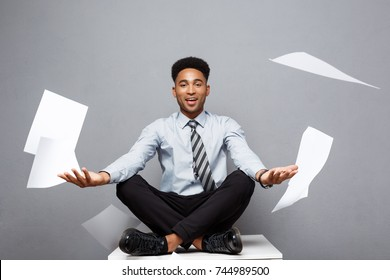 Business Concept - handsome young professional african american businessman throwing away pile of paperworks flying on air.