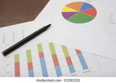 Business concept image. Pie chart and bar chart for analysis of sales. pen laying on the charts. Focus point on the bar charts.