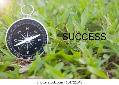 business concept image,compass and word succes over grass background.selective focus shot.
