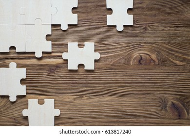 Business concept with  jigsaw puzzle on wooden background. Incomplete wooden puzzles on brown wooden desk, top view, flat lay. The concept of logical thinking, conundrum.