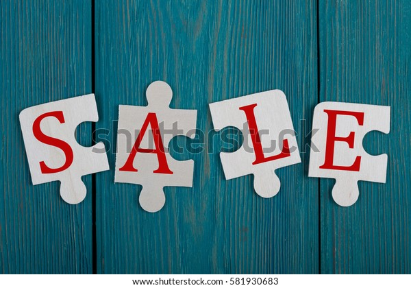 """Business Concept - Jigsaw Puzzle Pieces with text """"SALE"""" on blue wooden background"""