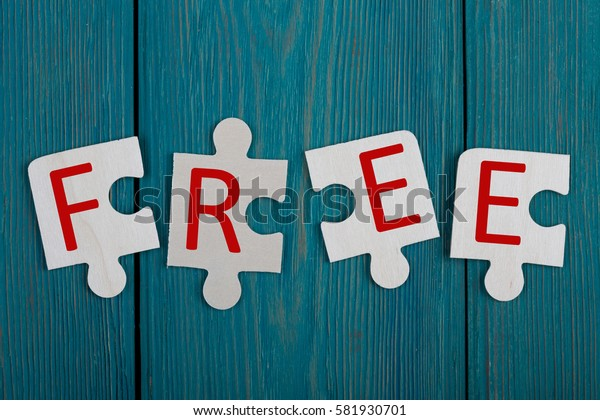 """Business Concept - Jigsaw Puzzle Pieces with text """"FREE"""" on blue wooden background"""