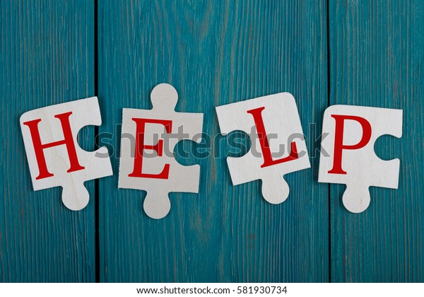 "Business Concept - Jigsaw Puzzle Pieces with words ""Help"" on blue wooden background"