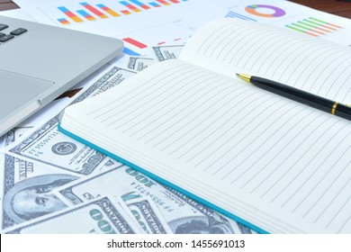 Business Concept. Laptop, graph and banknote dollars with notebook and pen