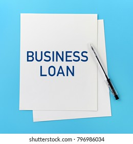 Business concept. Business Loan text on white paper, with a pen on blue background