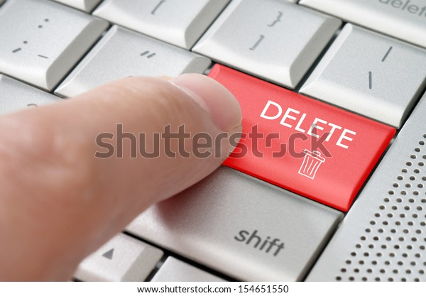 Business concept male finger pointing delete key on  a metallic keyboard