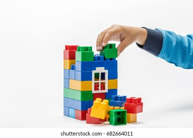 Business concept, man builds with plastic blocks on a white background