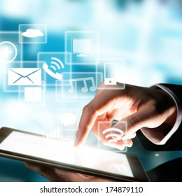 Business concept with man hand touching tablet computer. Virtual icons around