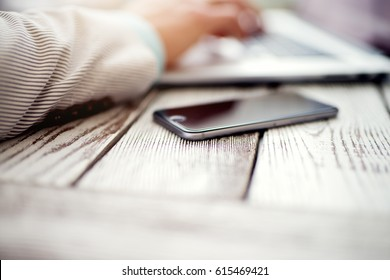 Business concept. Man typing laptop keyboard shallow depth of field. Smart phone in focus.