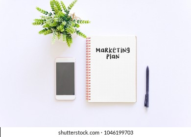 Business concept : Marketing plan word on notepad with smartphone and green plant, isolated white background